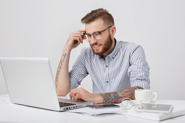 Handsome male copy writer works on new article, leans elbow on desk, uses laptop, smart phone, Free Photo