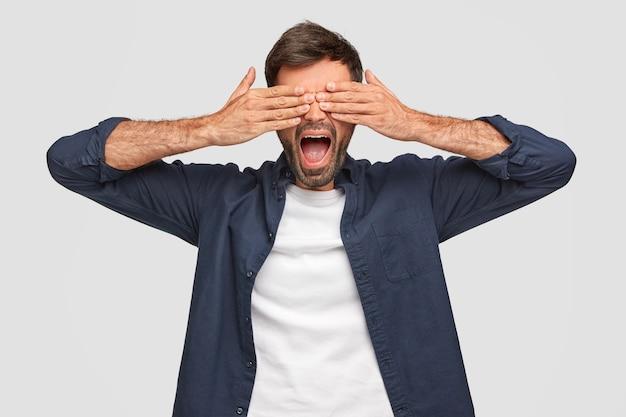 Bel maschio copre gli occhi con entrambe le mani, tiene la bocca ampiamente, ha la barba incolta, vestito con una camicia, aspetta la sorpresa, isolato su un muro bianco. il giovane barbuto fa capolino tra le dita. Foto Gratuite