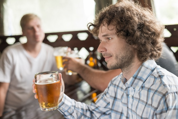 Handsome male drinking beer near friends in bar Free Photo