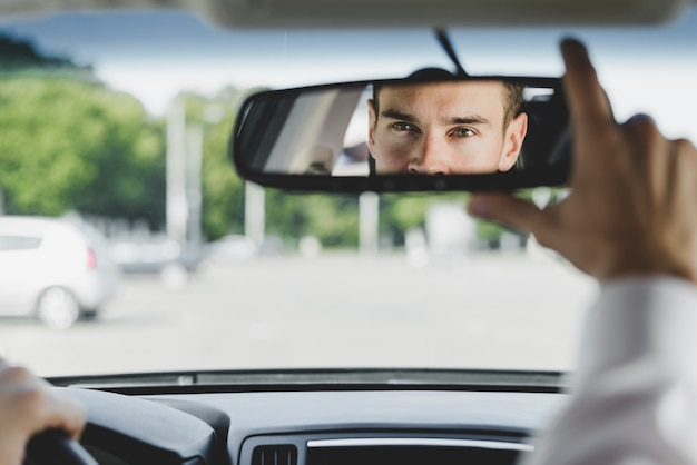 Handsome male driver adjusting the rearview mirror in the car Free Photo