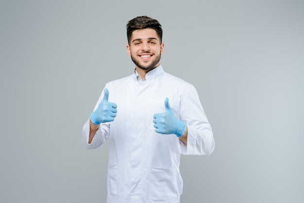 Handsome male medical doctor in gloves shows thumbs up isolated over grey background Premium Photo