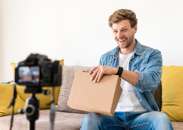 Handsome male recoding unboxing video at home Free Photo