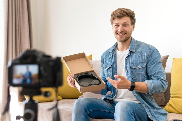 Handsome male recording unboxing video at home Free Photo