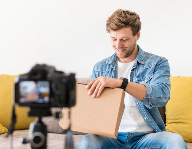 Handsome male recording while unboxing product Free Photo
