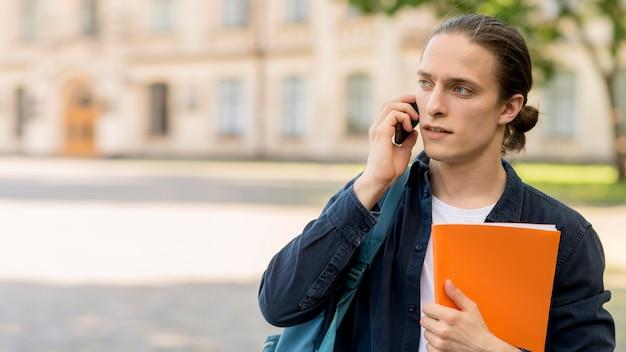 電話で話しているハンサムな男子生徒 無料写真