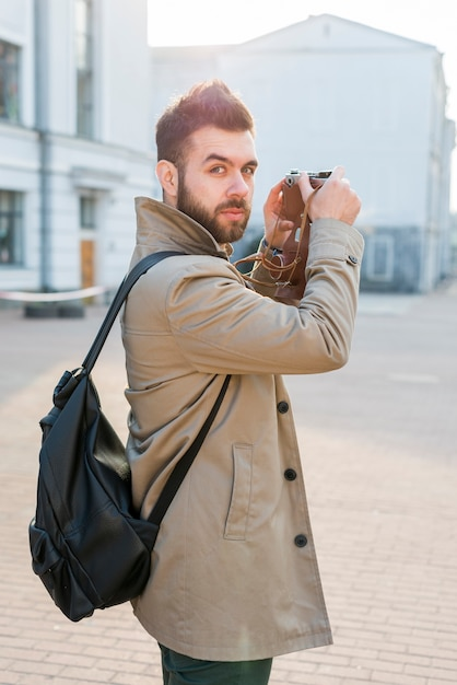 Handsome male traveler holding camera in hand looking at camera Free Photo