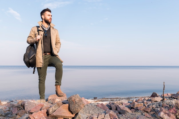 Handsome male traveler standing in front of sea holding handbag on shoulder looking away Free Photo