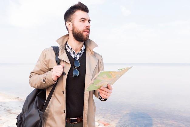 Handsome male traveler standing near the sea holding map in hand looking away Free Photo