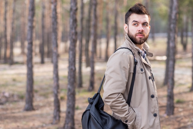 Handsome male traveler with backpack on his shoulder looking away Free Photo
