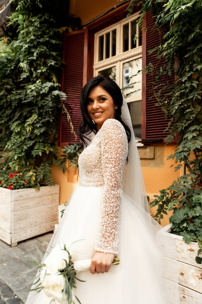 Handsome man or african american groom hugging pretty girl or cute bride with beautiful blond hair in white sexy wedding dress outdoors on blurred city street background Premium Photo