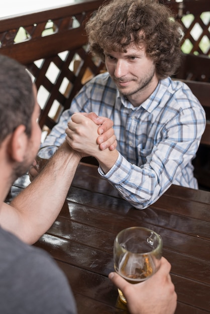Handsome man arm wrestling with friend in pub Free Photo