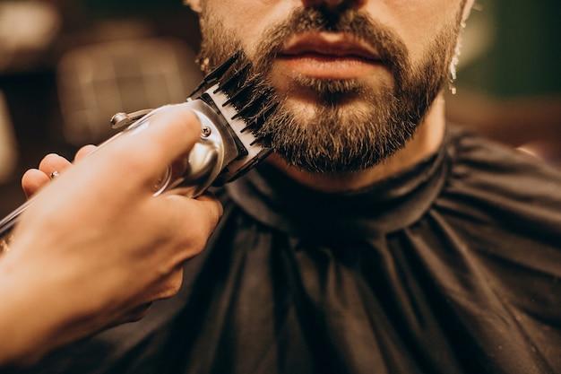 Uomo bello al barbiere di rasatura della barba Foto Gratuite