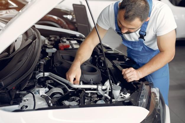 L'uomo bello in un'uniforme blu controlla l'automobile Foto Gratuite