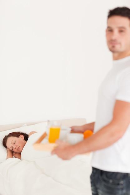 彼の眠っている妻に朝食をもたらすハンサムな男 Premium写真