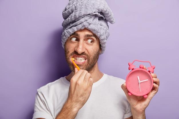 Красивый мужчина чистит зубы, отбеливает зубной пастой, держит в руке будильник, проснулся поздно утром, завернул голову в полотенце, носит повседневную белую футболку, изолированную на фиолетовой стене. утренняя рутина Бесплатные Фотографии