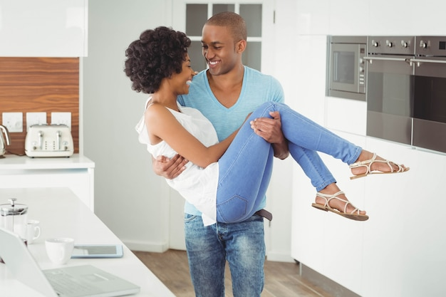 Handsome man carrying his girlfriend in the kitchen Premium Photo