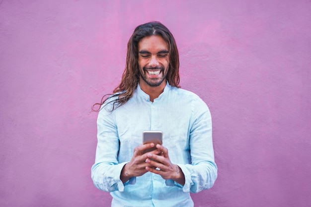 Handsome man in casual clothes  using a smartphone app with purple wall in background - young trendy guy having fun with new trends technology - tech and social generation concept - focus on his face Premium Photo