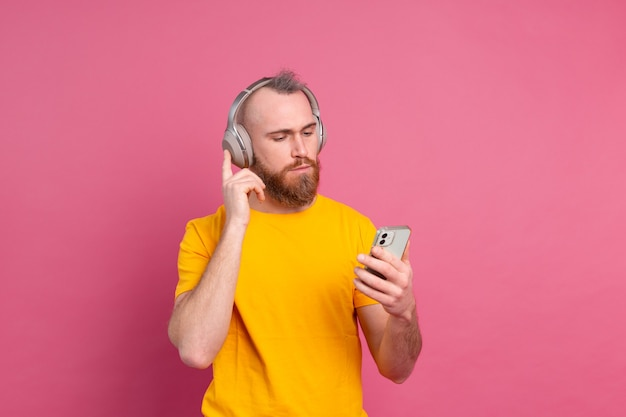 Handsome man in casual listening to music with headphones isolated on pink background Free Photo