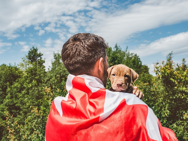 Handsome man and a charming puppy. close-up Premium Photo