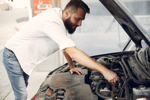 Handsome man checks the engine in his car Free Photo