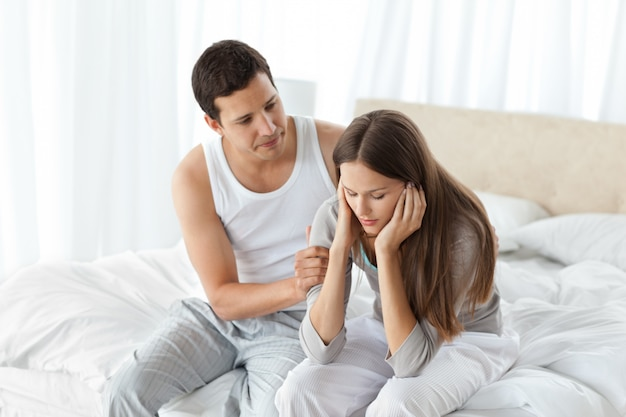 Handsome man comforting his girlfriend together on the bed Premium Photo