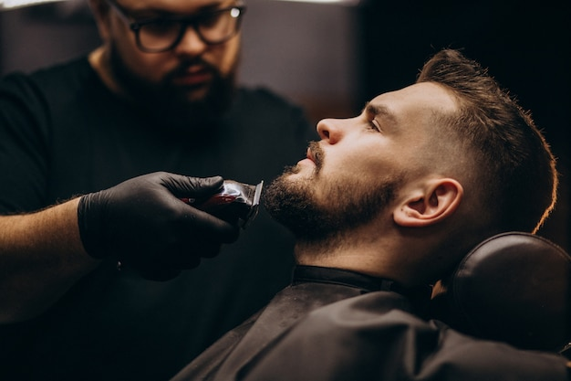 Handsome man cutting beard at a barber salon Free Photo