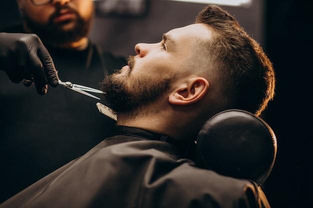 Handsome man cutting beard at a barber shop salon Free Photo