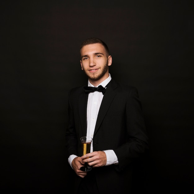 Handsome man in dinner jacket with glass of drink Free Photo