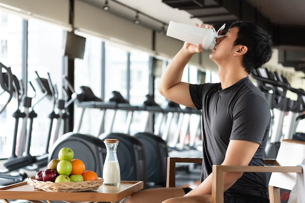 Handsome man drinking protein shake milk and many kind of fruits for nourishing body daily Premium Photo