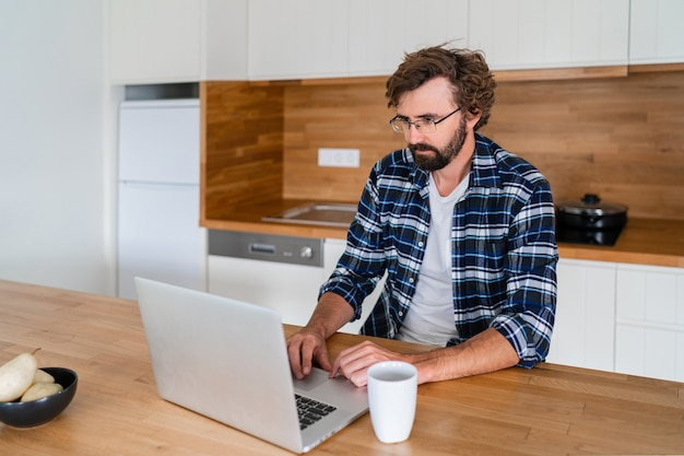 Handsome man freelancer using laptop studying online working from home Free Photo