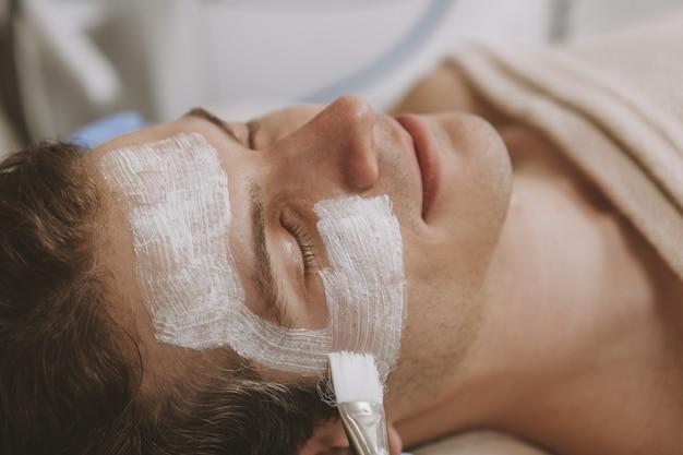 Handsome man getting facial skincare treatment Premium Photo