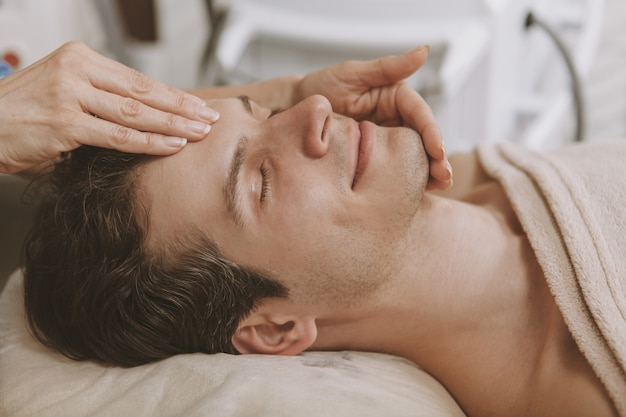 Handsome man getting facial skincare treatment Premium Photo