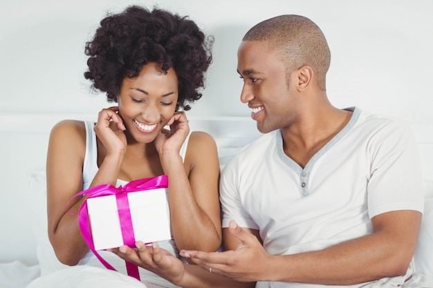 Handsome man giving present to his girlfriend on the bed Premium Photo