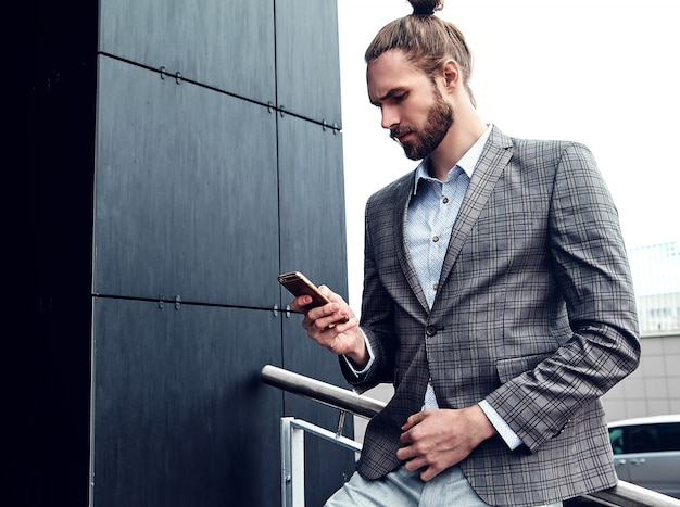 Handsome man in gray checkered suit with smartphone Free Photo