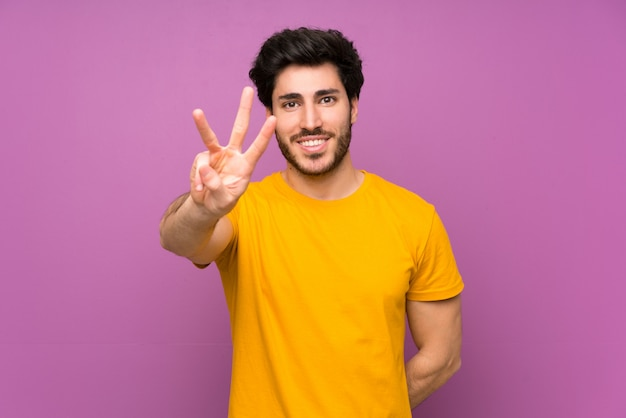 Handsome man happy and counting three with fingers Premium Photo