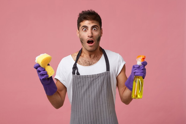 Uomo bello che ha la faccia sporca che indossa il grembiule e guanti che tengono la spugna e lo spray per la pulizia avendo un'espressione scioccata realizzando quanto dovrebbe pulire. uomo perplesso che fa le faccende domestiche isolate Foto Gratuite