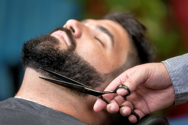 Handsome man having a shave with scissors at the barbershop. Premium Photo