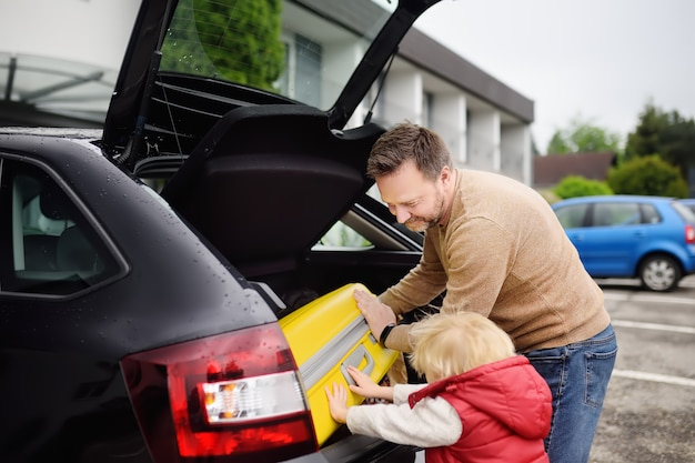 Handsome man and his little son going to vacations, loading their suitcase in car trunk Premium Photo
