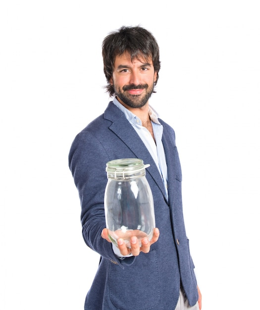 Handsome Man Holding An Empty Glass Jar Over Isolated