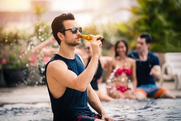 ビール瓶を持ってプールパーティーを楽しむハンサムな男 Premium写真