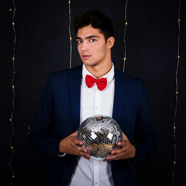 Handsome man holding disco ball Free Photo