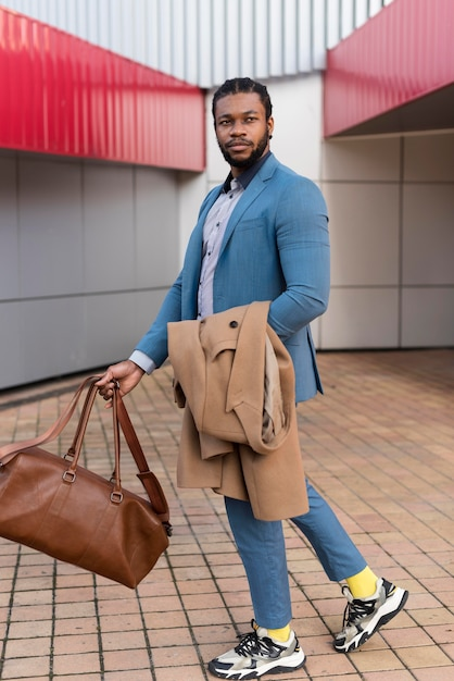 Handsome man holding his bag Free Photo
