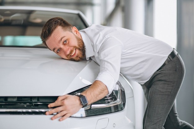 Handsome man hugging a car in a showroom Free Photo