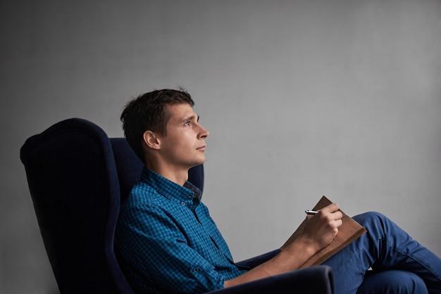 暗い椅子に座って、メモ帳でアイデアを書く青いシャツとジーンズのハンサムな男 無料写真