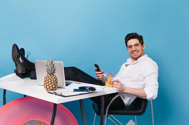 Красивый мужчина в очках и офисном наряде смотрит в камеру с улыбкой, держит смартфон, наслаждается коктейлем и сидит за столом с ноутбуком, надувным кругом и ананасом. Бесплатные Фотографии