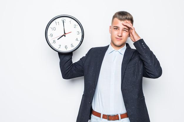 スイートのハンサムな男は、白い、後期の概念に分離された片手で大きな時計を保持します 無料写真