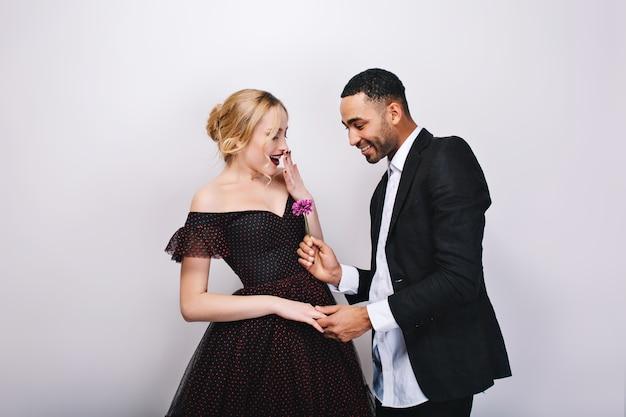 Красивый мужчина в смокинге, дающий цветок красивой молодой блондинке в роскошном вечернем платье. удивленные, радостные, счастливые моменты, день святого валентина, подарок, любовь, вместе. Бесплатные Фотографии
