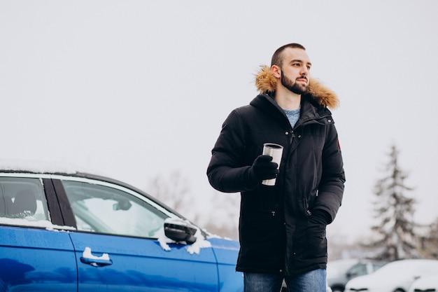 Красивый мужчина в теплой куртке стоит у машины, покрытой снегом, и пьет кофе Бесплатные Фотографии