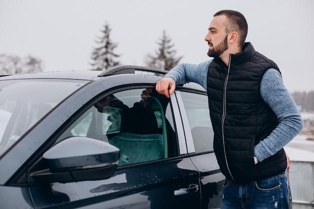 雪に覆われた車のそばに立っている暖かいジャケットのハンサムな男 無料写真