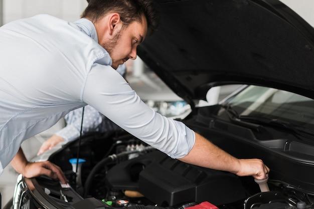 Handsome man inspecting car engine Free Photo
